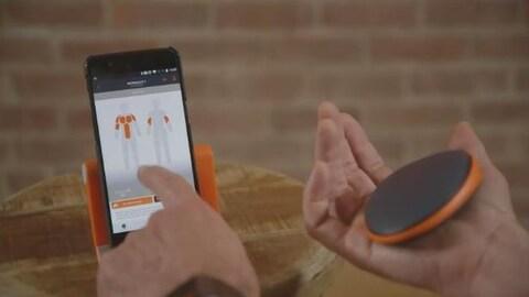 Un homme touche l'écran d'un téléphone intelligent de sa main gauche et tient un gadget en forme de petit coussin dans sa main droite.