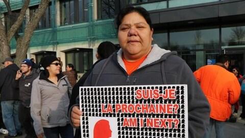 Une femme manifeste devant le palais de justice de Val-d'Or. Elle tient une pancarte sur laquelle on peut lire : « Suis-je la prochaine? Am I next? »