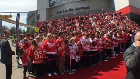 Une foule est devant l'aréna avec leurs chandails des Red Wings. On peut voir des milliers de personnes.