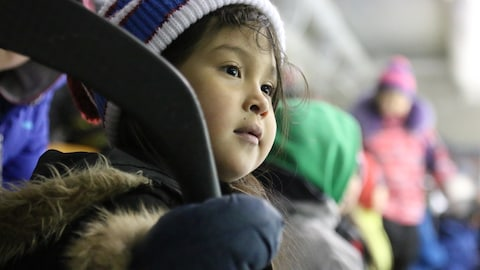 Fillette inuit dans l'assistance d'un match de hockey, à Salluit, Nunavik.
