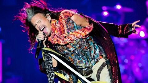 Steven Tyler, qui porte une tenue très colorée, chante au micro sur scène.