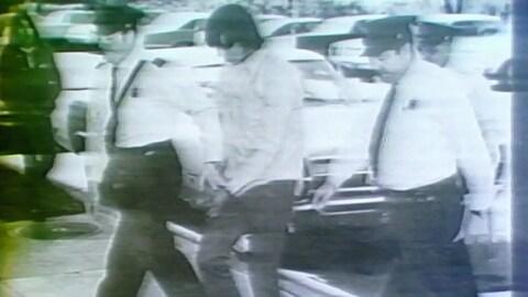 Donald Marshall, menotté, escorté par des policiers.