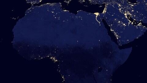 Le Nord du  continent africain vu de l'espace, la nuit, alors que peu de points lumineux indiquent la présence d'éclairage électrique.