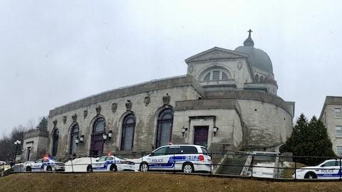 Des véhicules de police sont garés devant l'oratoire, sous les flocons.