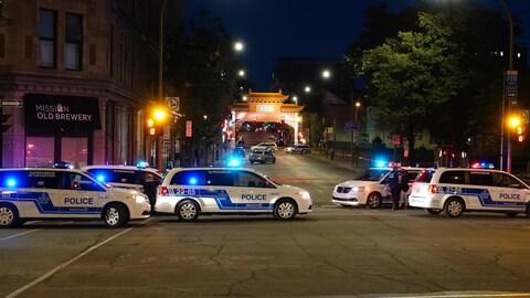 Des voitures de police barrent une rue dans la nuit. La pagode illuminée nous montre que nous sommes sur le boulevard Saint-Laurent