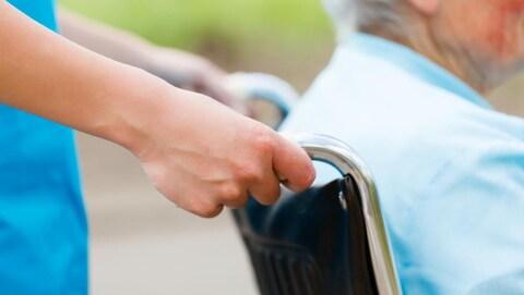 Une infirmière pousse une chaise roulante.