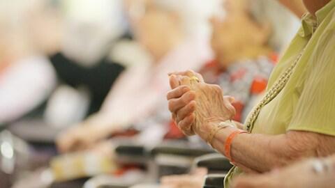 Les mains d'une aînée en centre.