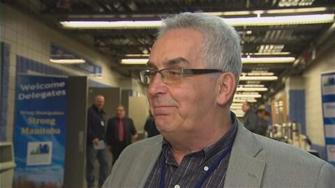 Louis Tétrault porte des lunettes et regarde à sa droite dans le couloir d'un bâtiment