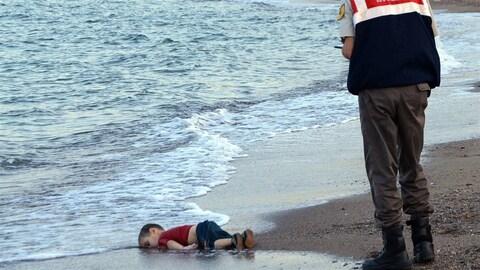 Un jeune garçon repose mort face contre terre sur le bord d'une plage.