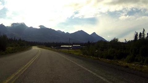 Une route rejoint l'horizon, au coeur d'un paysage nordique et montagneux.