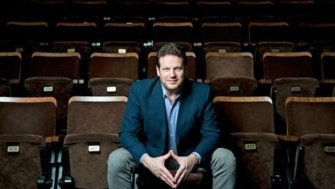 Albert Schultz assis sur des bancs de théâtre dans une salle