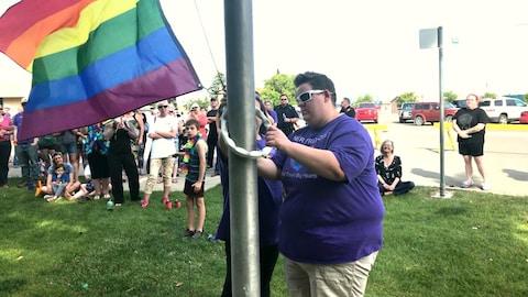 Deux personnes fixent le drapeau arc-en-ciel de la fierté à un mât, devant quelques dizaines de spectateurs.