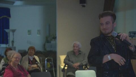 Un jeune homme chante devant des personnes âgées.