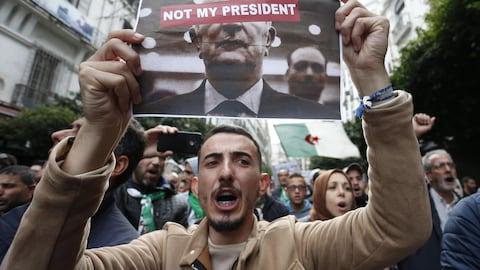 """Un homme brandit une feuille sur laquelle est imprimé une photo de M. Tebboune, sur laquelle a été superposée la note """"Pas mon président"""", en anglais."""