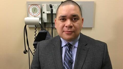 Un homme en veston et cravate dans une salle d'évaluation de médecin.