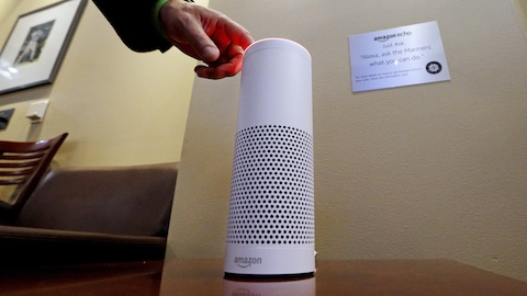 Une main allume l'assistant personnel intelligent Echo, un appareil fabriqué par Amazon