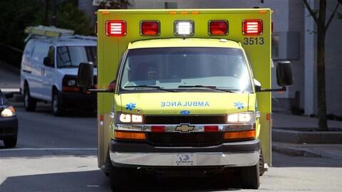 Une ambulance, phares allumés, tourne sur un coin de rue
