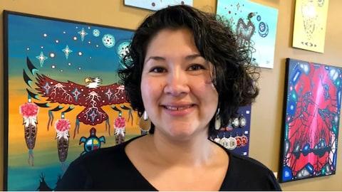 Gros plan du visage d'une femme souriante. Derrière elle on peut voir de l'art autochtone.