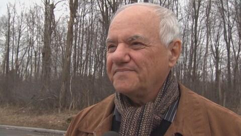 André Guay en entrevue à Radio-Canada, à l'extérieur, devant des arbres