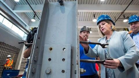 Andrea avec un casque de travail bleu manie un outil