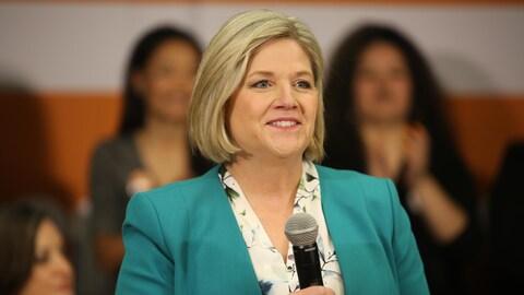 Andrea Horwath debout devant des supporteurs avec un micro à la main.