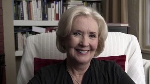 Une dame avec des cheveux blonds-blancs, sourit à la caméra.