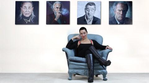 Angela Hardy assise devant quelques-unes de ses oeuvres.