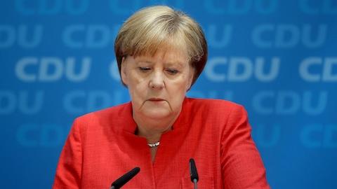 Angela Merkel, les yeux baissés, en conférence de presse.