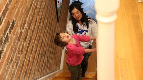 Une petite fille handicapée monte les marches des escaliers de sa maison, aidée par sa maman.