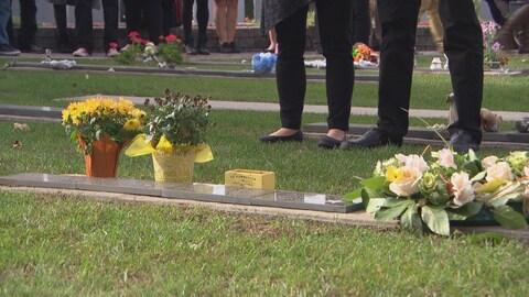 Des gens se recueillent devant des plaques à la mémoire de jeunes enfants décédés en bas âge.