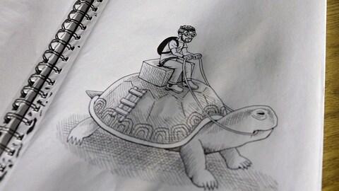 Une feuille de papier sur laquelle on voit le dessin d'Anthony Woodward, en noir et blanc. Il s'est dessiné sur le dos d'une tortue.