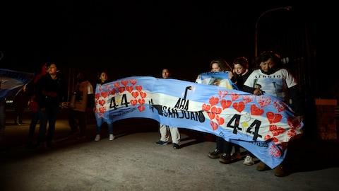 Des gens tiennent une banderole sur laquelle on peut lire ARA San Juan, avec le chiffre 44, entouré de coeurs.