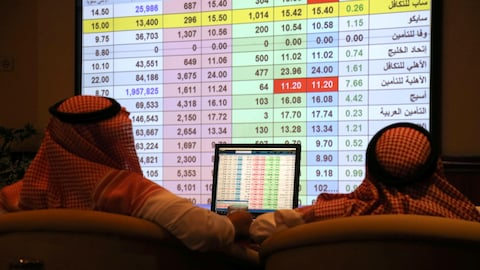 Saudi men inspect a screen showing stock prices at ANB Bank in Riyadh, Saudi Arabia September 16, 2019. REUTERS/Stringer NO RESALES. NO ARCHIVES. - RC1133C069F0