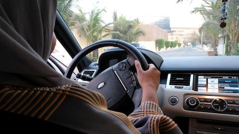 Une femme saoudienne au volant d'une voiture.