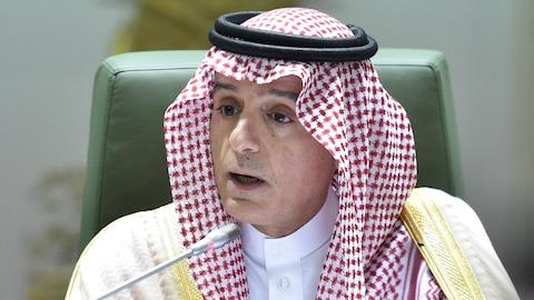 Un homme portant une tenue traditionnelle saoudienne parle devant un micro.