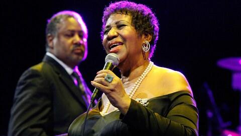 Aretha Franklin chante, les yeux fermés, alors qu'on voit un de ses musiciens en arrière-plan, lors d'un concert à New York en 2011.