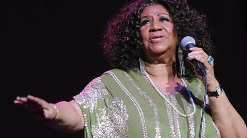 La chanteuse a des cheveux longs noirs et frisés, elle tient un micro et tend l'autre main.