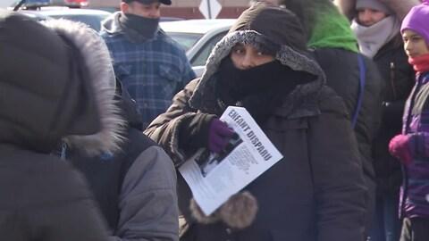 Une femme tient une affiche avec le visage du jeune Ariel Jeffrey Kouakou.