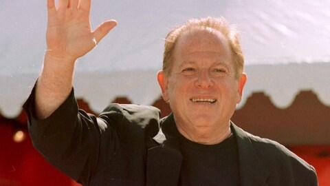 L'homme salue les gens en levant sa main.