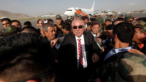 Un homme en costume noir et cravate rouge portant des lunettes de soleil est accueilli par la foule à sa descente d'avion.