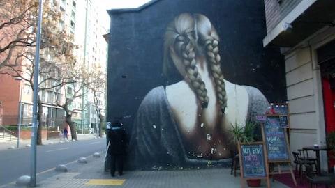 Une femme malvoyante consultant la plaque en relief et la description en Braille accompagnant une peinture urbaine à Santiago, au Chili.