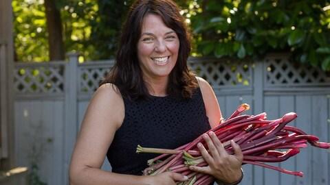 Une femme tient des tiges de rhubarbe dans ses bras.