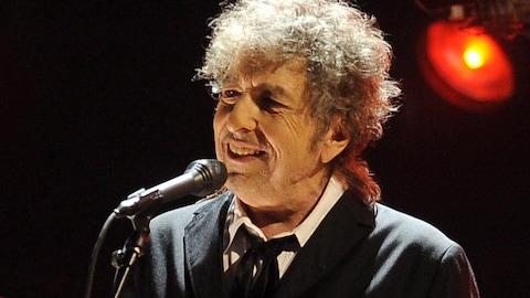 L'artiste Bob Dylan sourit alors qu'il se tient devant un micro.