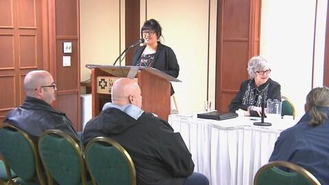 Une femme parle au micro devant des journalistes et des citoyens.