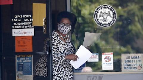 Une femme masquée se glisse dans l'entrebâillement d'une porte, formulaire en main.