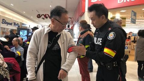Un policier est en train d'attacher un brassard à une personne âgée.