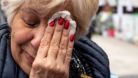 Une femme âgée tient un mouchoir sur l'un de ses yeux, l'autre est fermé.