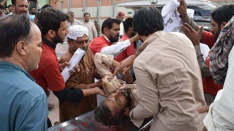 Un homme blessé est placé sur un brancard par une dizaine d'autres hommes