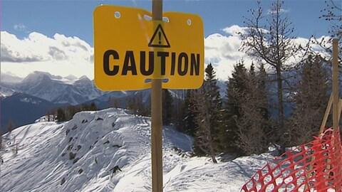 Une affiche jaune indiquant « ATTENTION » au sommet d'une montagne enneigée.