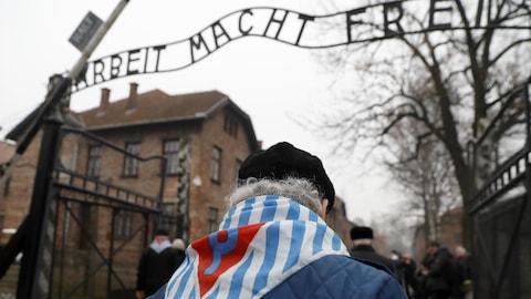 Un homme passe sous l'enseigne de l'entrée de l'ancien camp de concentration d'Auschwitz où est écrit en allemand «Arbeit macht frei», le travail rend libre.